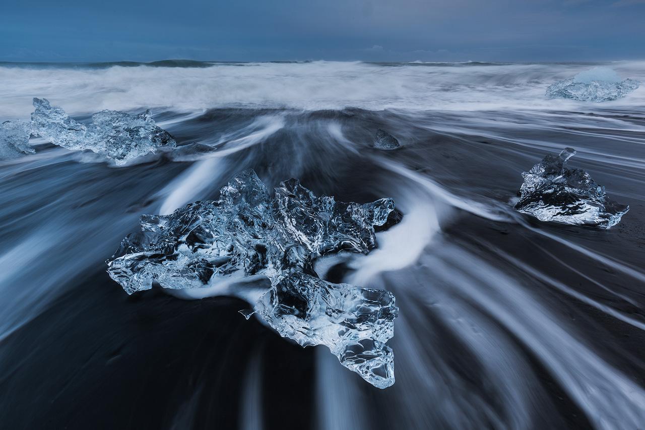 ก้อนน้ำแข็งที่ใสอย่างน่าเหลือเชื่อไหลเอื่อยๆไปยังไดมอนด์บีชในชายฝั่งทางใต้ของประเทศไอซ์แลนด์.