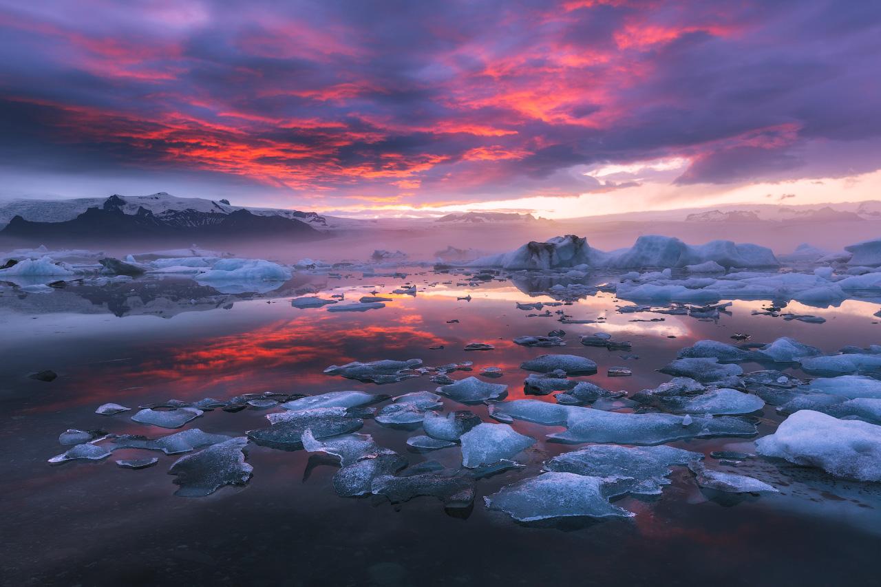 Ein zauberhafter Sonnenuntergang in der Gletscherlagune Jökulsárlón lässt den Himmel in rosarotem Licht erstrahlen.