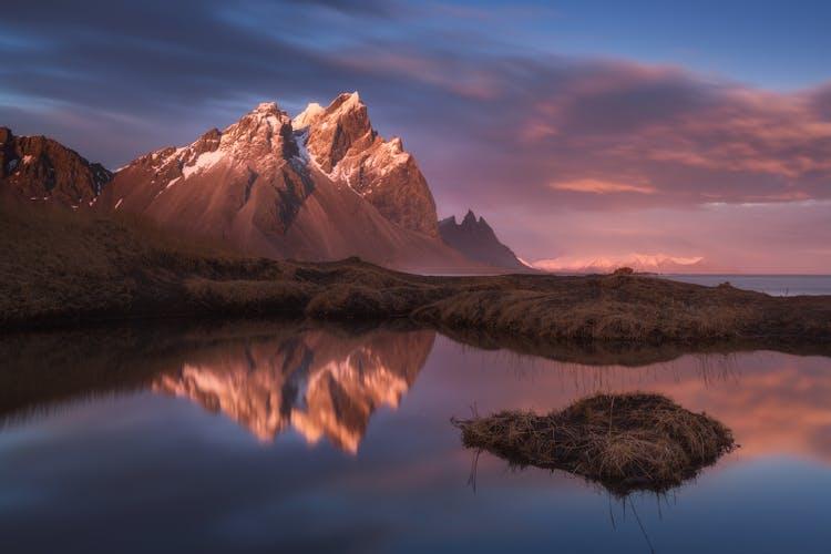 一座山脉及其在冰岛东部清澈平静水面上的倒影。