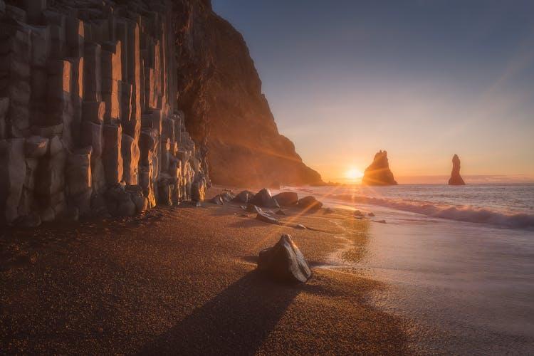 Der schwarze Sandstrand Reynisfjara kurz bevor die Sonne hinter den dramatischen Felsnadeln Reynisdrangar untergeht.