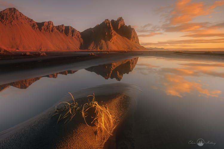 Mount Vestrahorn rises up over the Stokksnes peninsula, here you can see it reflected in the shiny black sands.