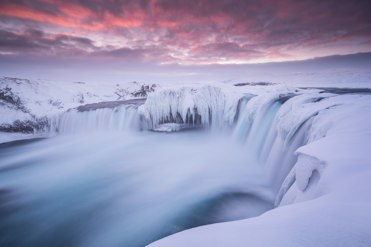 Goðafoss waterfall resembles an icy gnarled monster in the depths of winter as it freezes in places.