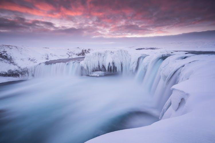 La cascade de Goðafoss ressemble à un monstre glacé et noueux au plus profond de l'hiver alors qu'il gèle par endroits.