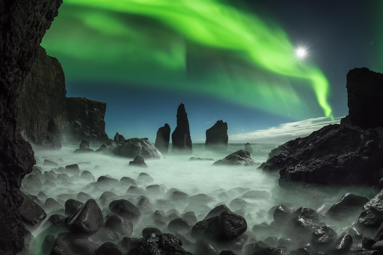 Nordlichter tanzen über dunklen Felsformationen auf der Halbinsel Reykjanes.