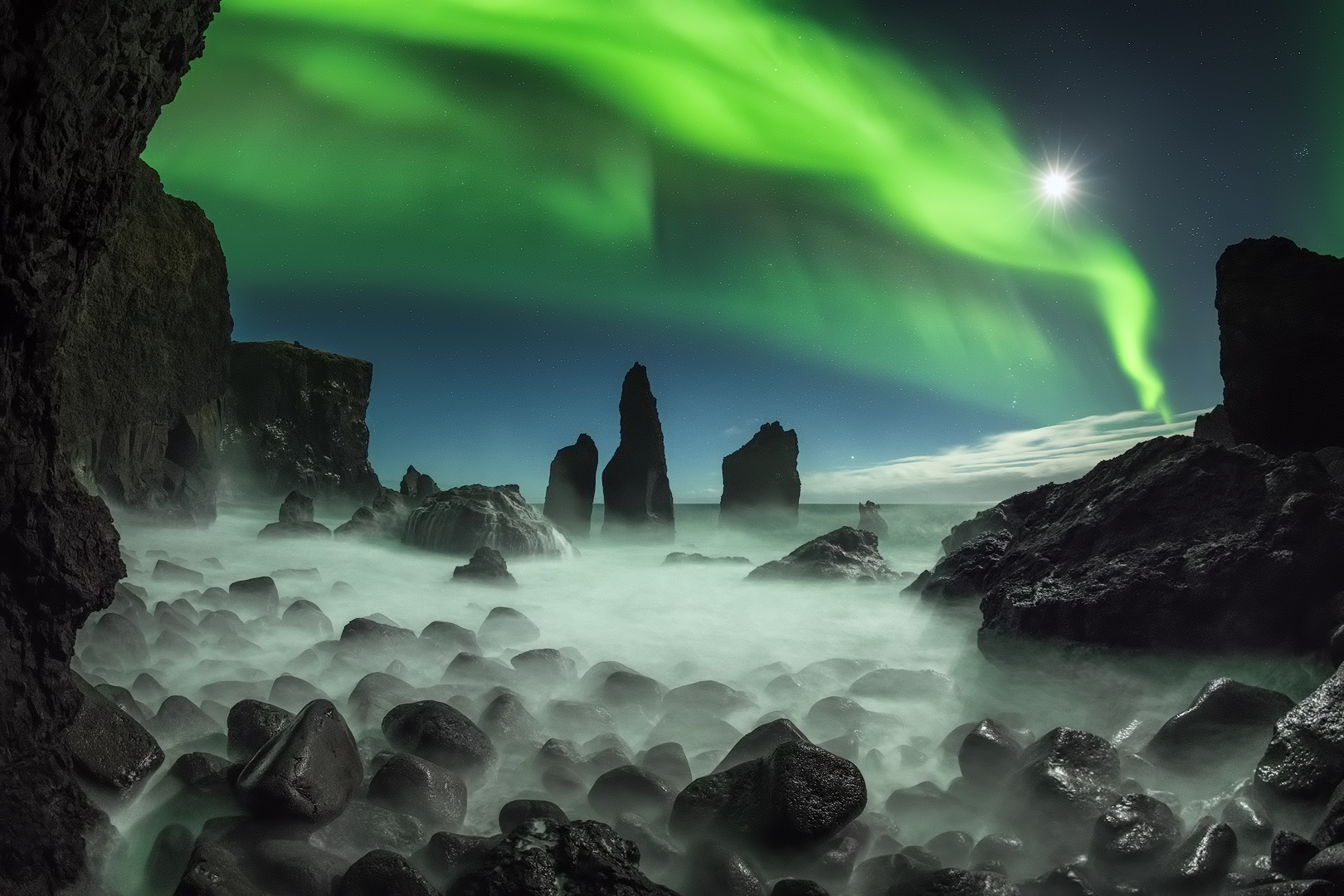 Northern Lights dancing over dark rock formations on the Reykjanes peninsula.