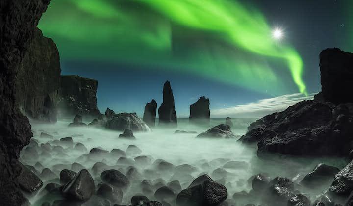 Northern Lights dancing over dark rock formations on the Reykjanes peninsula.