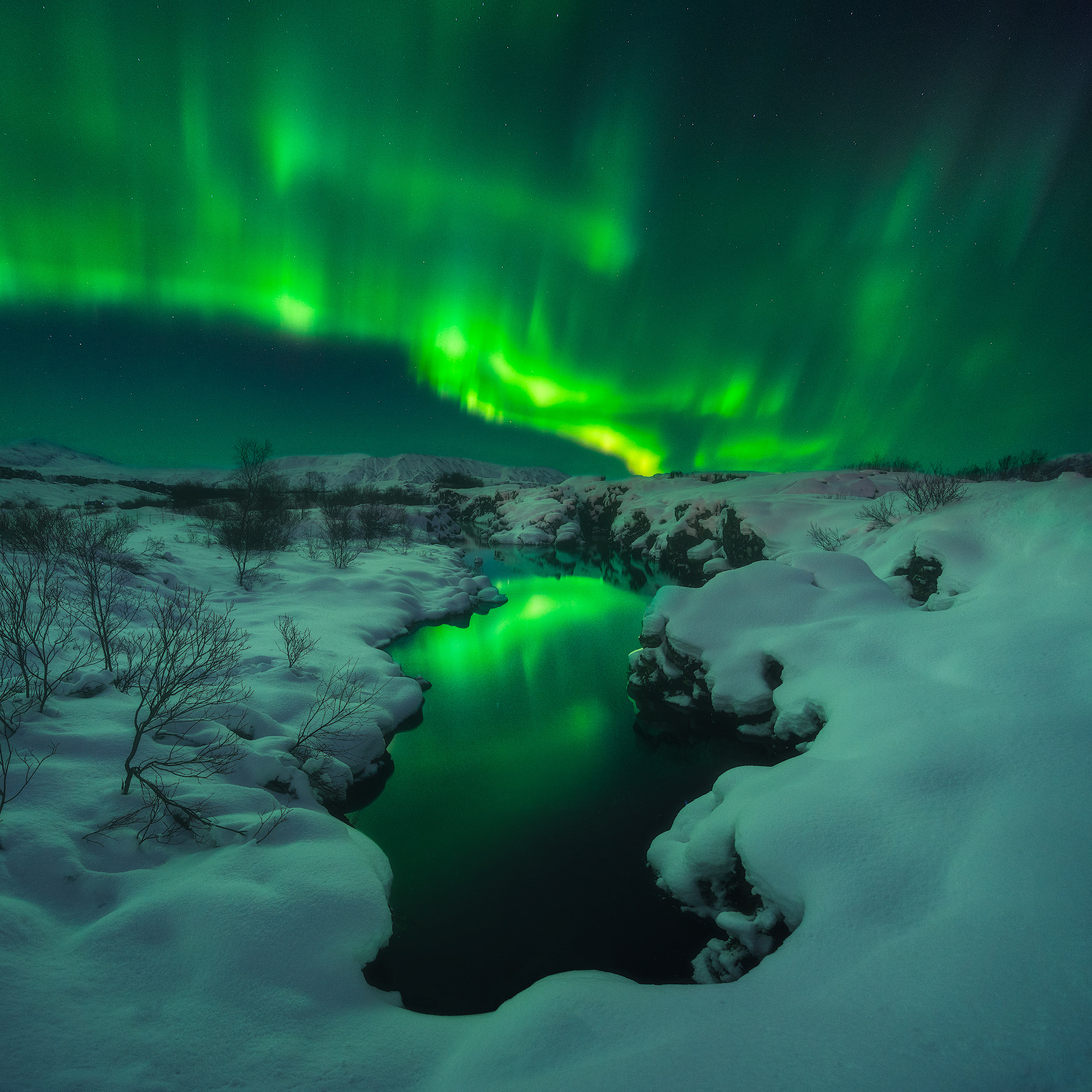 The Northern Lights swirling around in the sky above Þingvellir National Park.
