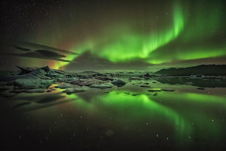 绿色的北极光在杰古沙龙冰河湖上空盘旋。