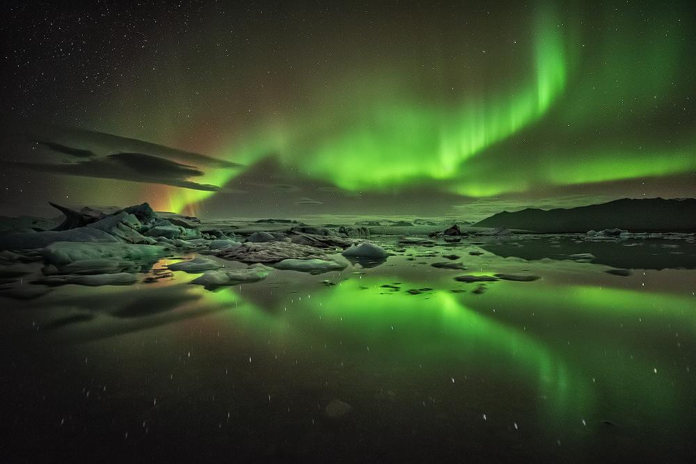 The green Northern Lights hanging over Jokulsarlon glacier lagoon.
