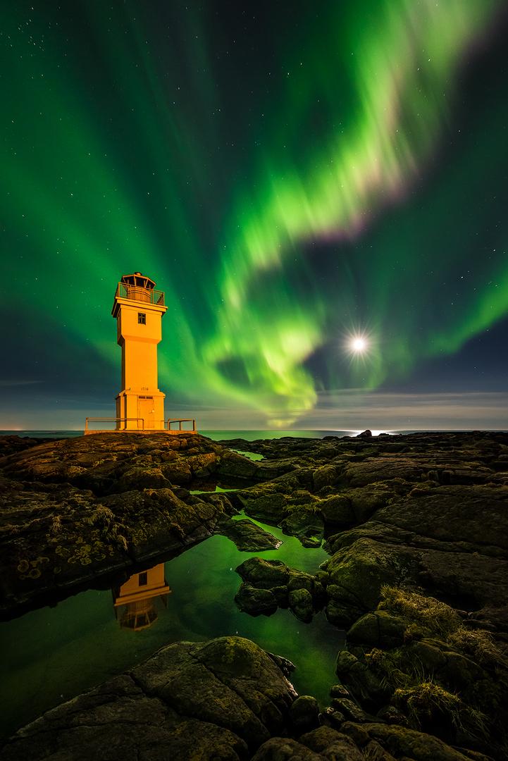 แสงออโรร่าเต้นรำอยู่เหนือหนึ่งในประภาคารของประเทศไอซ์แลนด์.