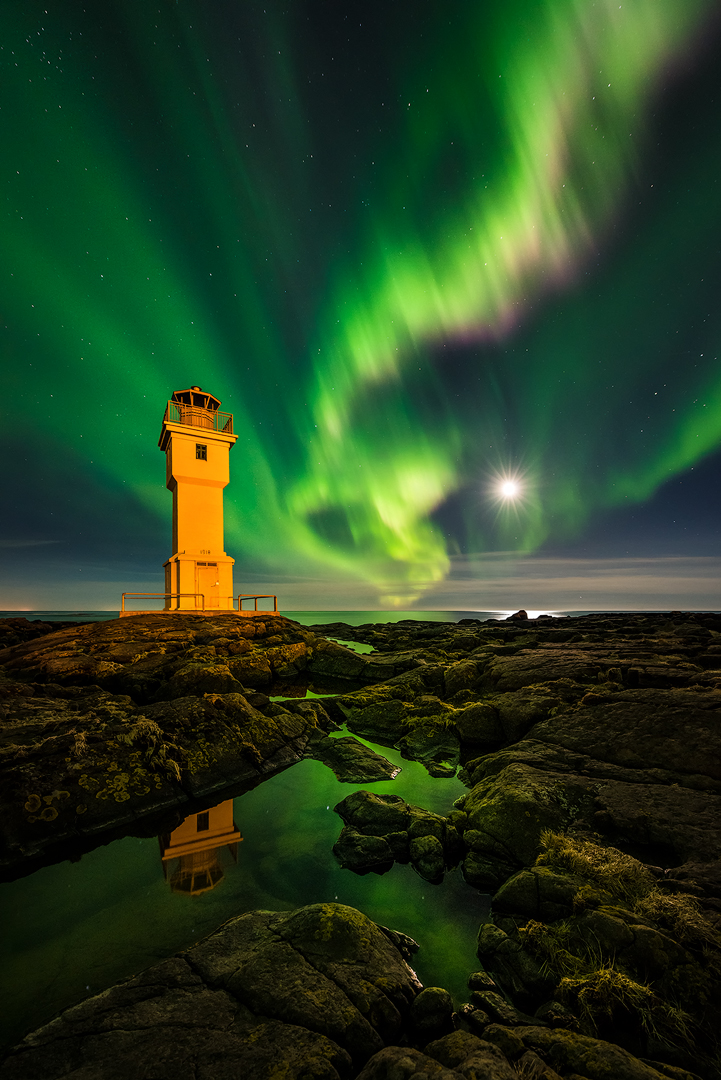 The Aurora Borealis dances above one of Iceland's lighthouses.
