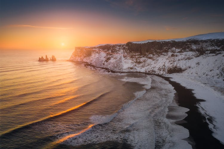 Black sands, white snow and golden sunset at Reynisfjara black sand beach.