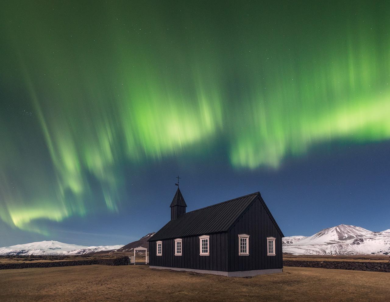 在冰岛的秋季,可以看到图片中的北极光在黑教堂Buðir后方翩翩起舞。