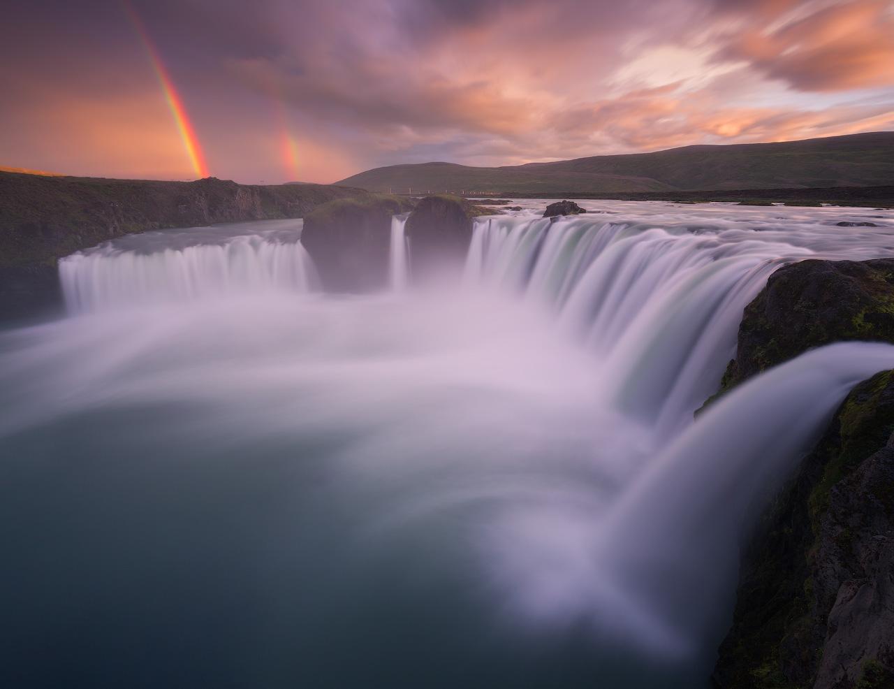 The mighty and beautiful waterfall Goðafoss thunders into the Skjálfandafljót river accompanied by a gorgeous rainbow.