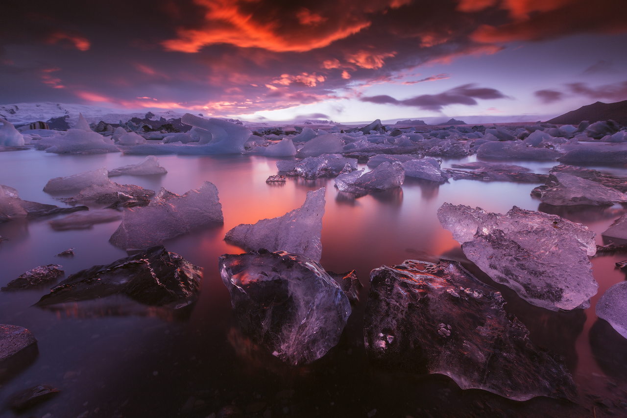 Icebergs glisten and reflect the warm colours of a sunset at Jökulsárlón glacier lagoon in the southeast of Iceland.