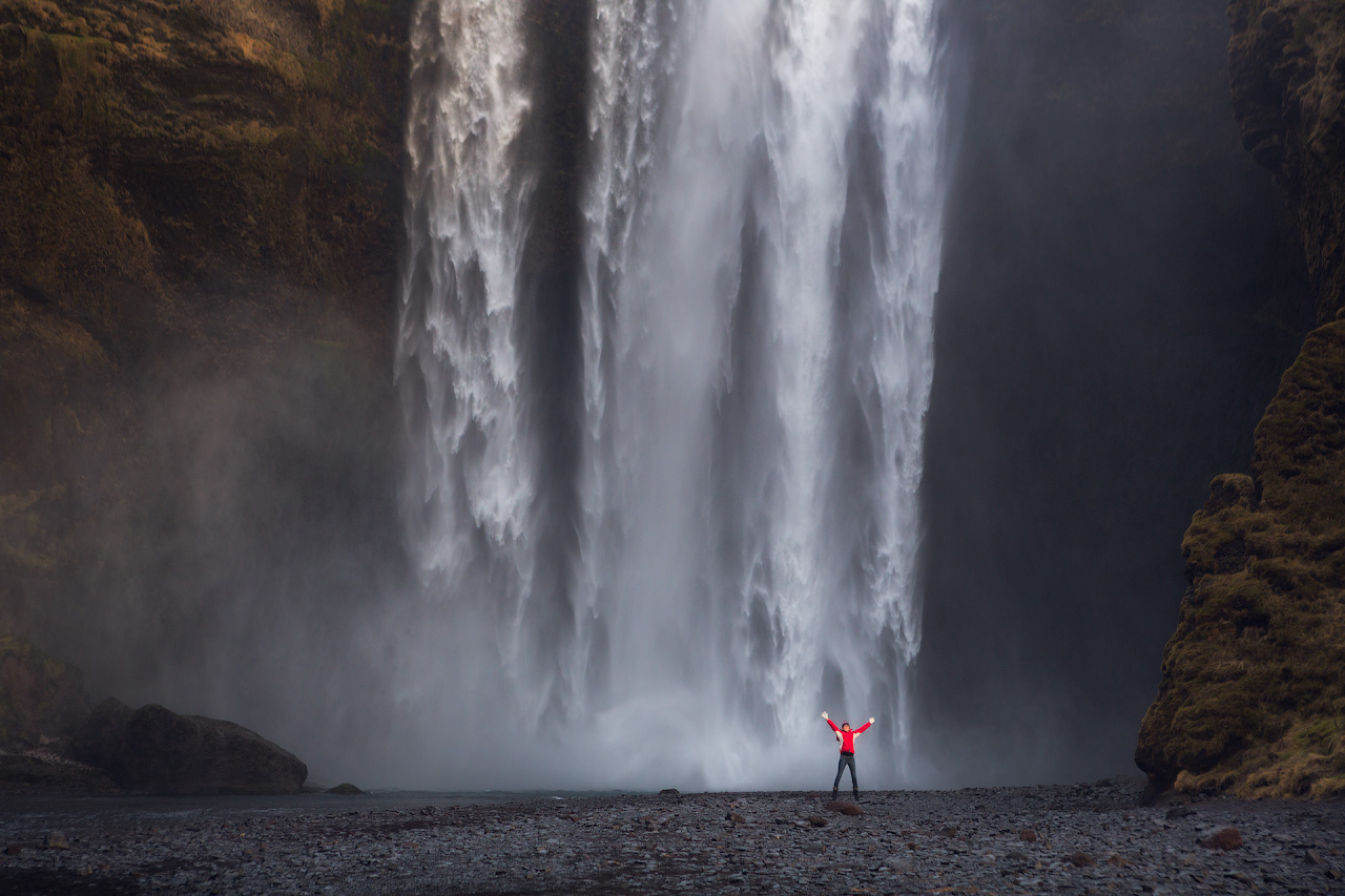 Here, a visitor stands up close to the large waterfall Skógafoss; the ground leading up to the falls in exceptionally flat, allowing you to walk right up to the water.