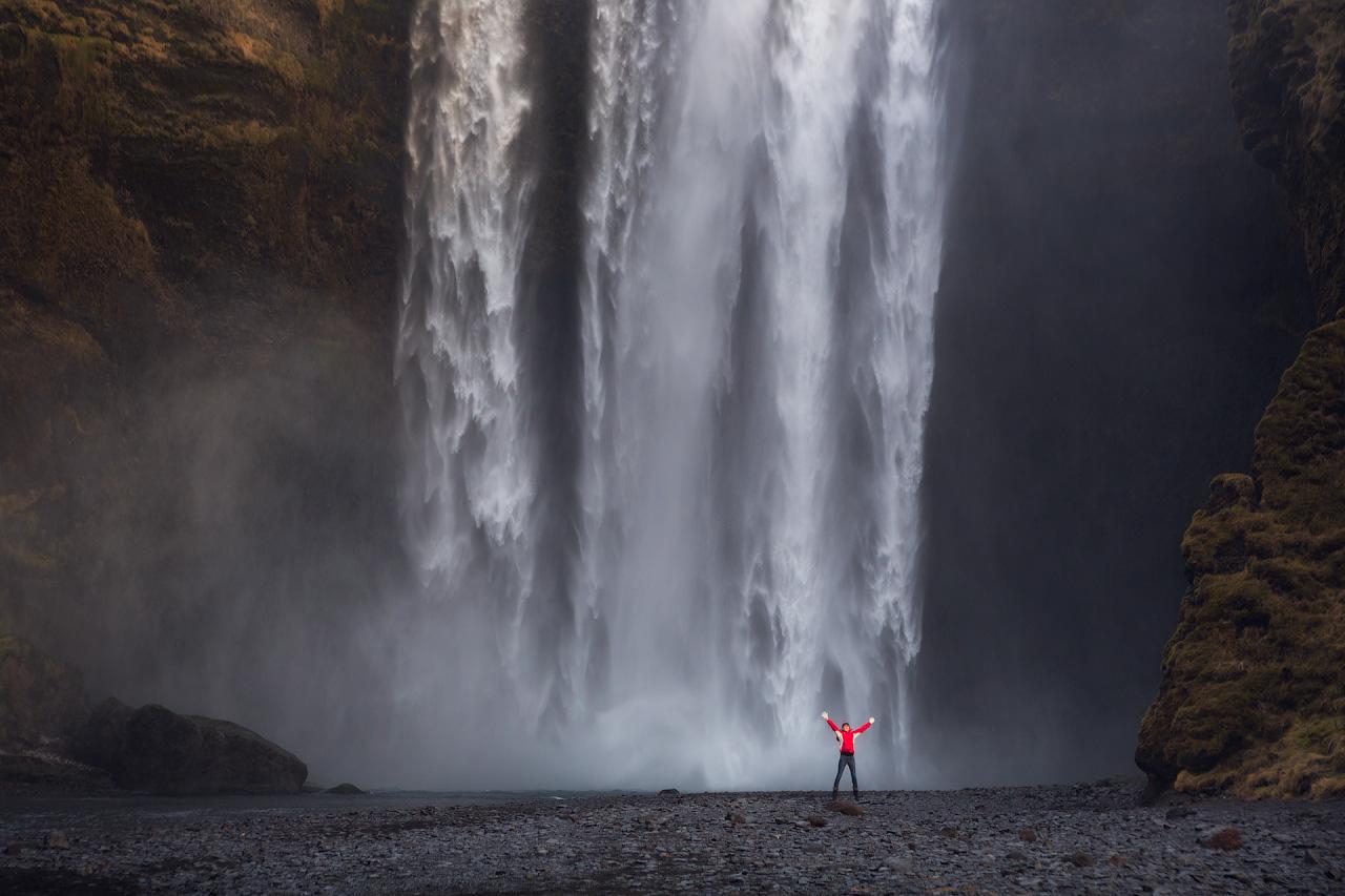 Hier steht ein Besucher an dem mächtigen Wasserfall Skogafoss. Der Boden unter der Kaskade ist so flach, dass man ganz nah herangehen kann.