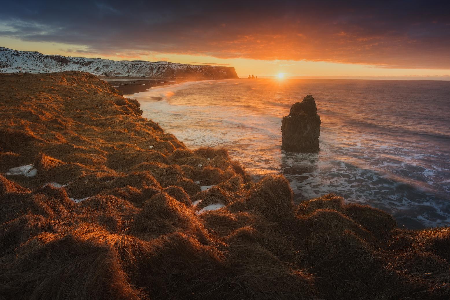 Die Sonne geht über Islands Südküste mit ihren vielen dramatischen Felsnadeln unter.