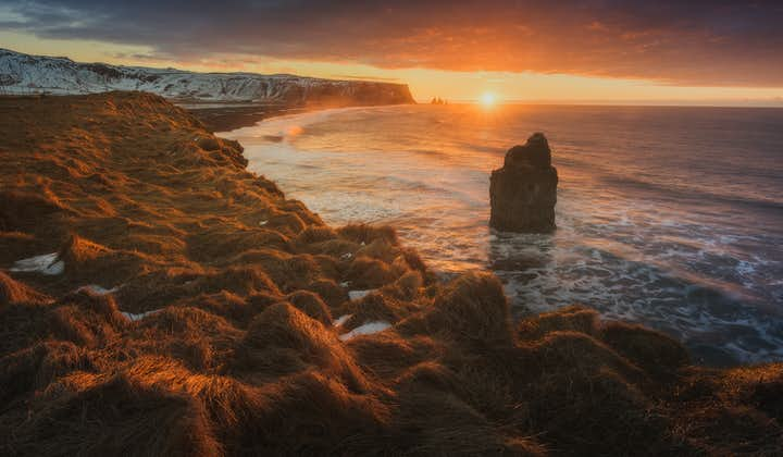 The sun setting over Iceland's South Coast dotted with dramatic sea stacks.