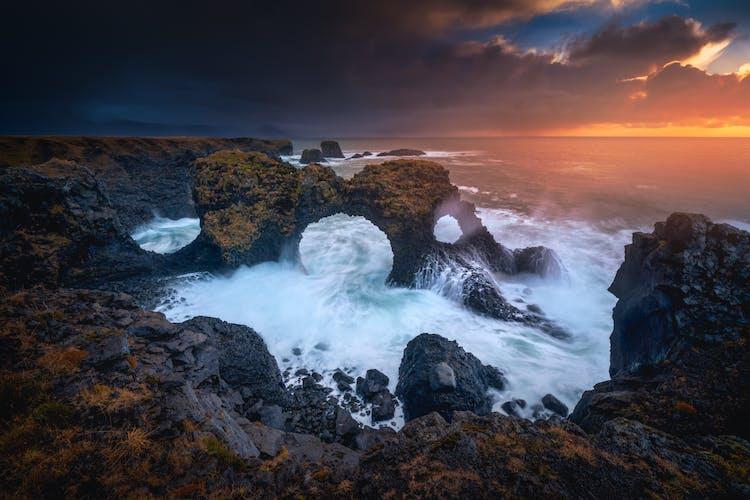 Der beeindruckende Felsbogen Gatklettur unter dem stimmungsvollen Himmel des isländischen Sommers.