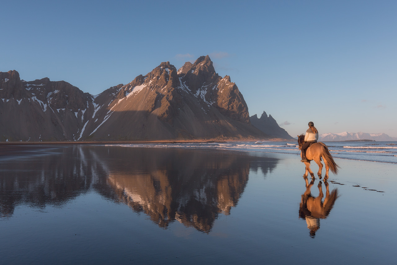 A horse ride galloping on the Stokknes Peninsula, just in front of Vestrahorn Mountain.