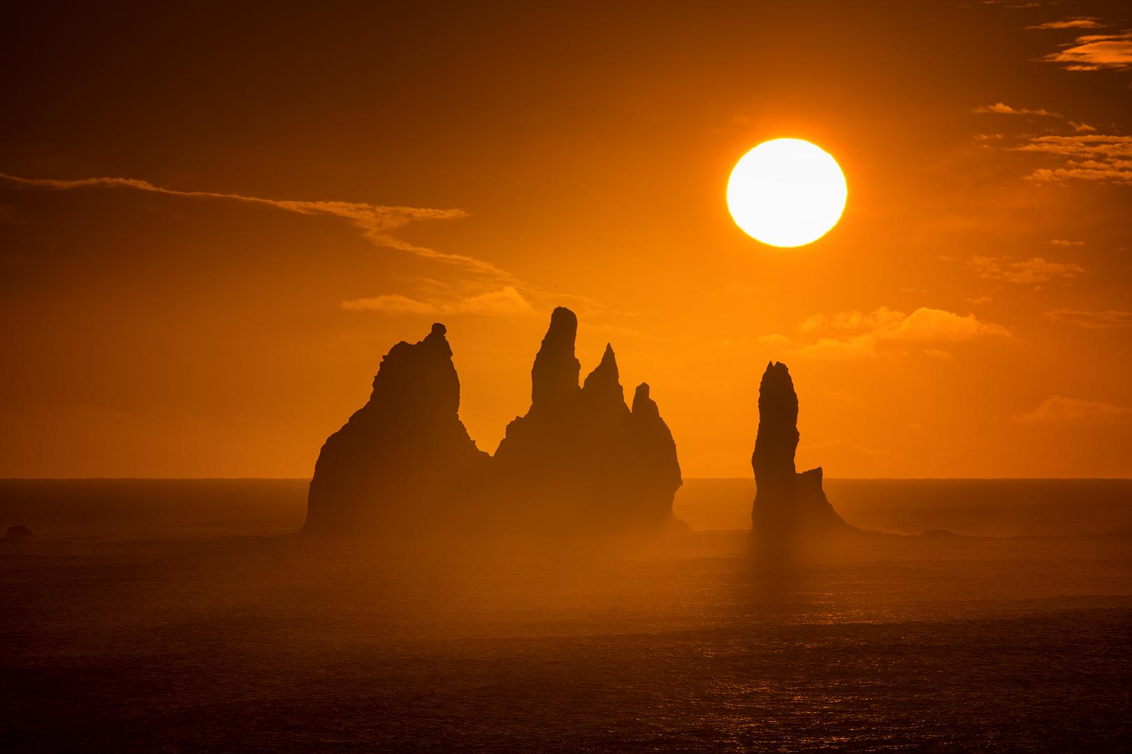 Il sole di mezzanotte splende sul mare, appena fuori dalla costa, sulla spiaggia di sabbia nera di Reynisfjara.