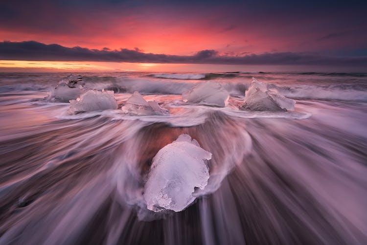 Eisberge funkeln wie Diamanten auf einem schwarzen Sandstrand in der Nähe der Gletscherlagune Jökulsarlon.