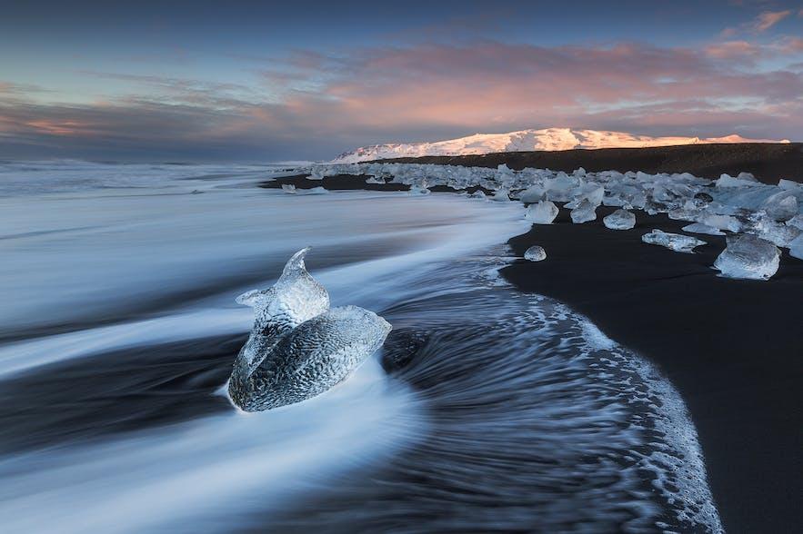 Auf dem Weg zu den Eishöhlen kannst du noch die wundervollen Fotomöglichkeiten in der Gletscherlagune Jökulsarlon auskosten, wo riesige Eisbrocken mit den Gezeiten über das Wasser treiben, und am nahegelegenen Breiðamerkursandur – besser bekannt als 'Eisstrand' – wo Eisbrocken wie Diamanten am schwarzen Sandstrand verstreut liegen.