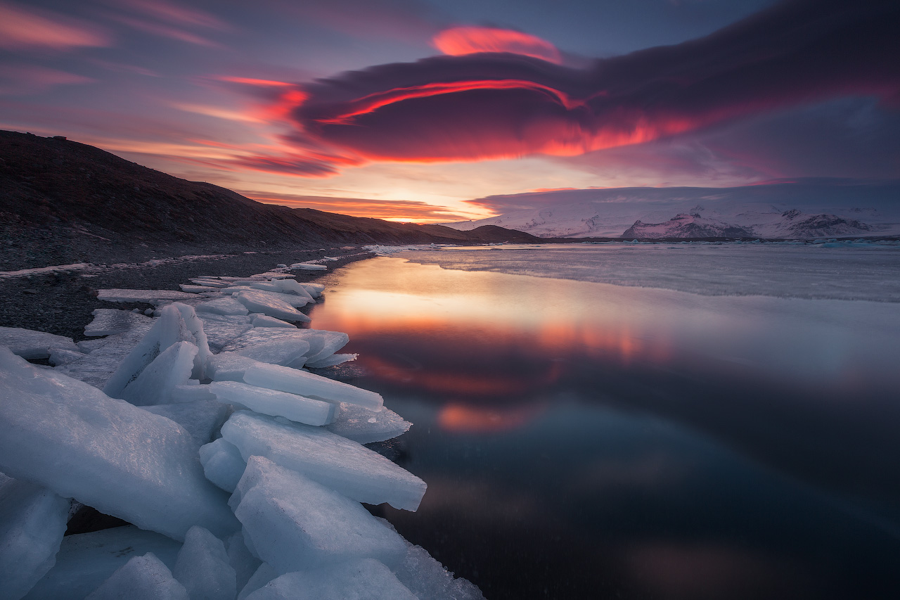 Arena negra, nieve blanca y una dorada puesta de sol en la playa de arena negra Reynisfjara.