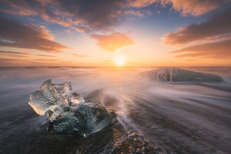 The sun rises over a coastal landscape scene of waves swirling around ice - Iceland Photography | Everything You Need To Know