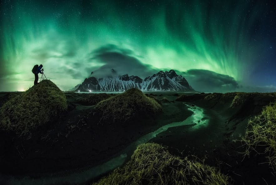 A photographer captures the northern lights flashing above a mountainous range at night time - Iceland Photography | Everything You Need To Know
