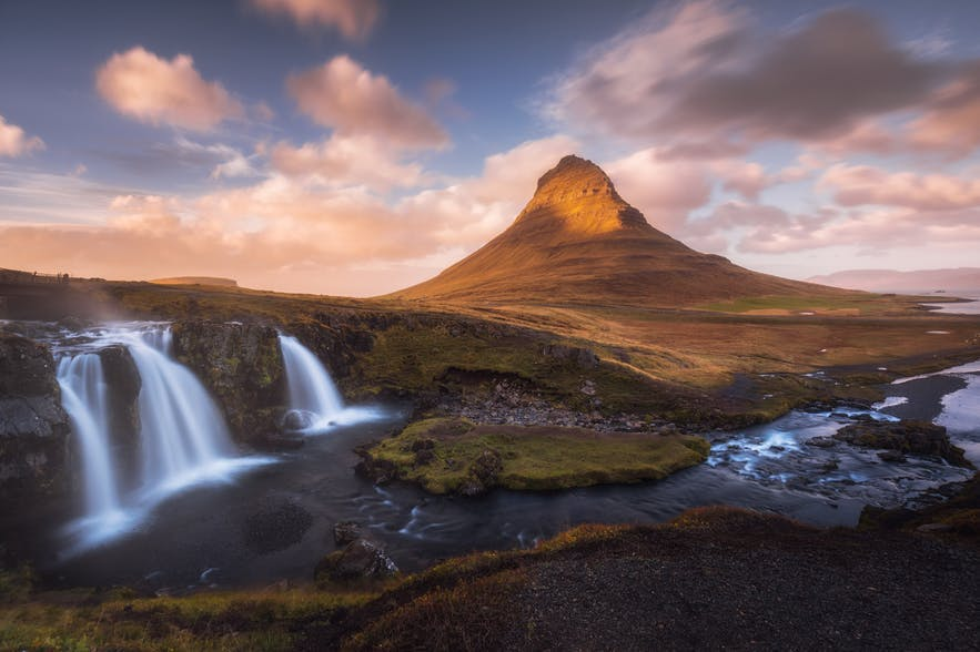 A mountain sits in the background of a typical Iceland landscape of waterfalls and rivers - Iceland Photography | Everything You Need To Know