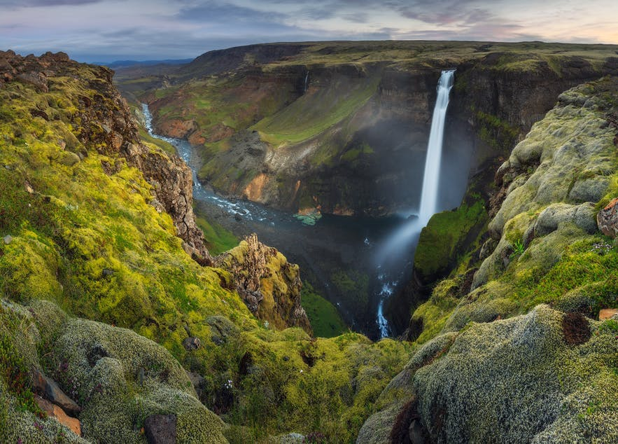 A waterfall peaks through between a rocky mountainous region - Iceland Photography | Everything You Need To Know