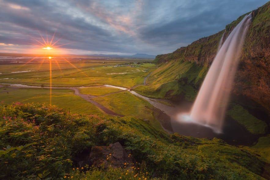 A waterfall seems like cotton wool as it pours over the Icelandic landscape as the sun rises - Iceland Photography | Everything You Need To Know