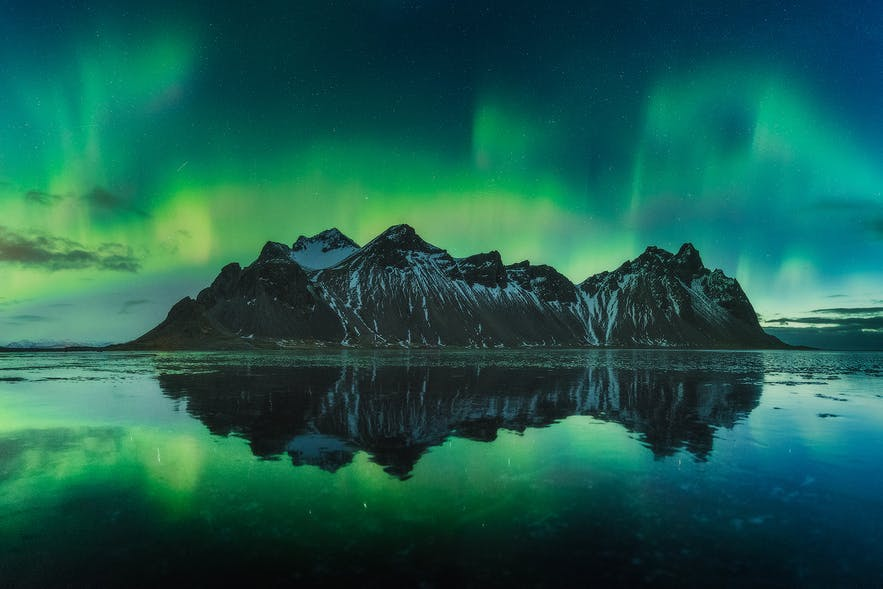 The northern lights dance above a mountain range - Iceland Photography | Everything You Need To Know