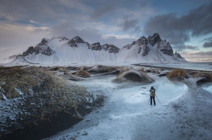 A photographer captures a typical Iceland landscape in front of a snowy mountain range - Iceland Photography | Everything You Need To Know