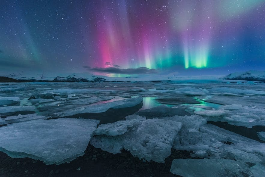 Bright lights flash in the night time sky above a landscape of broken ice - Iceland Photography | Everything You Need To Know
