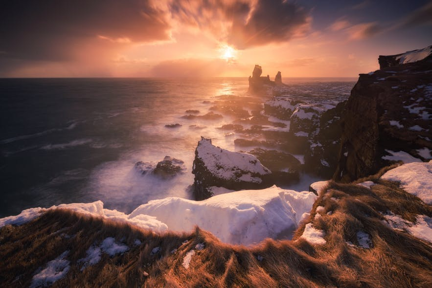 The sun sets over the rocky coast of Iceland - Iceland Photography | Everything You Need To Know