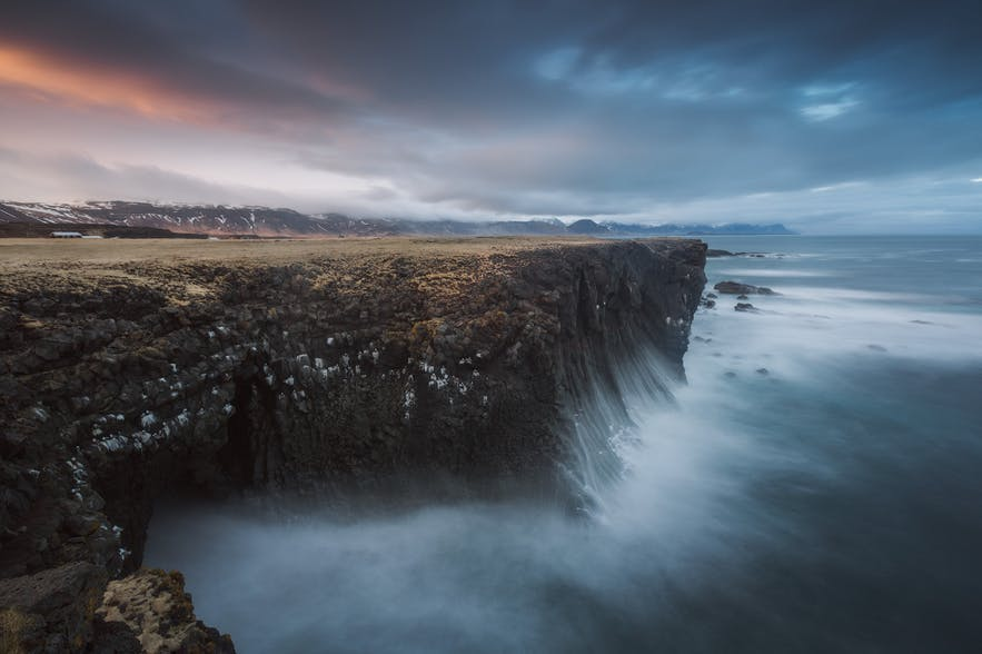 Waves smash against the side of a cliff face along the Icelandic coast - Iceland Photography | Everything You Need To Know