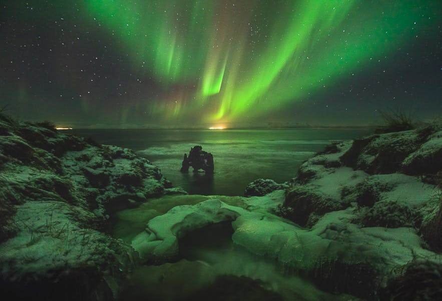 The Aurora flashes in the night skies above the Icelandic coast and rock column - Iceland Photography | Everything You Need To Know