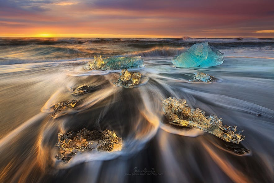 Waves swirl around ice on the beach during a long exposure scene - Iceland Photography | Everything You Need To Know