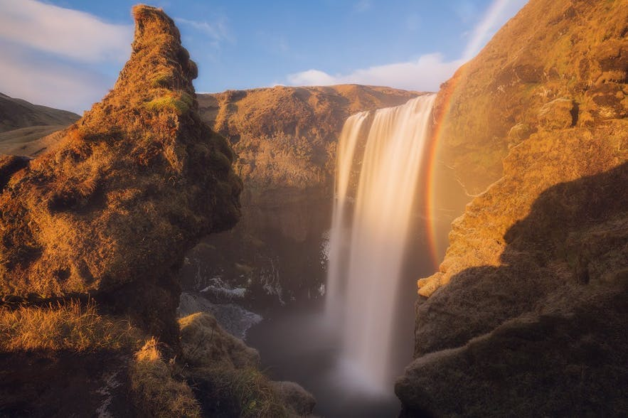 Alt Text: A rainbow appears next to a waterfall - Iceland Photography | Everything You Need To Know