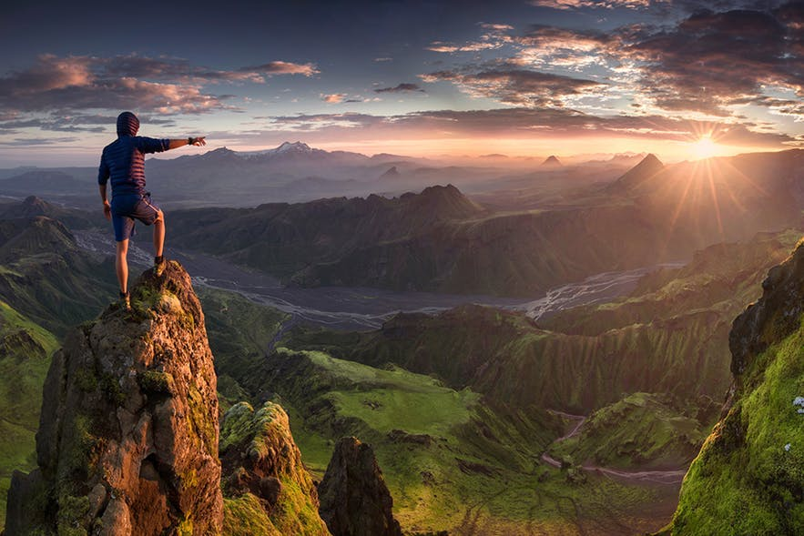 A man stands of a rock column close to the camera, pointing to a sunrise over the mountains - Iceland Photography | Everything You Need To Know