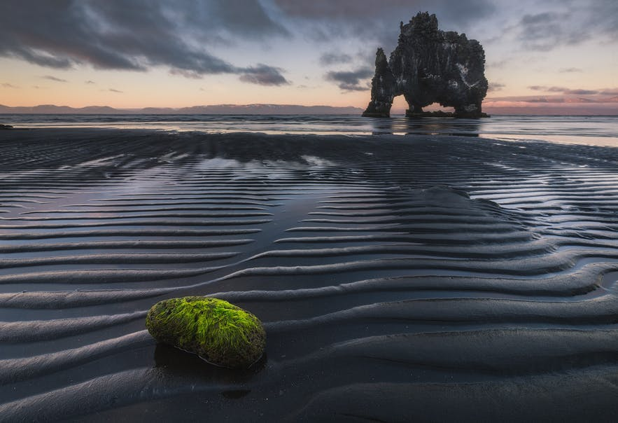 A mossy rock in the foreground leads to a rock formation that sticks out of the sea - Iceland Photography | Everything You Need To Know