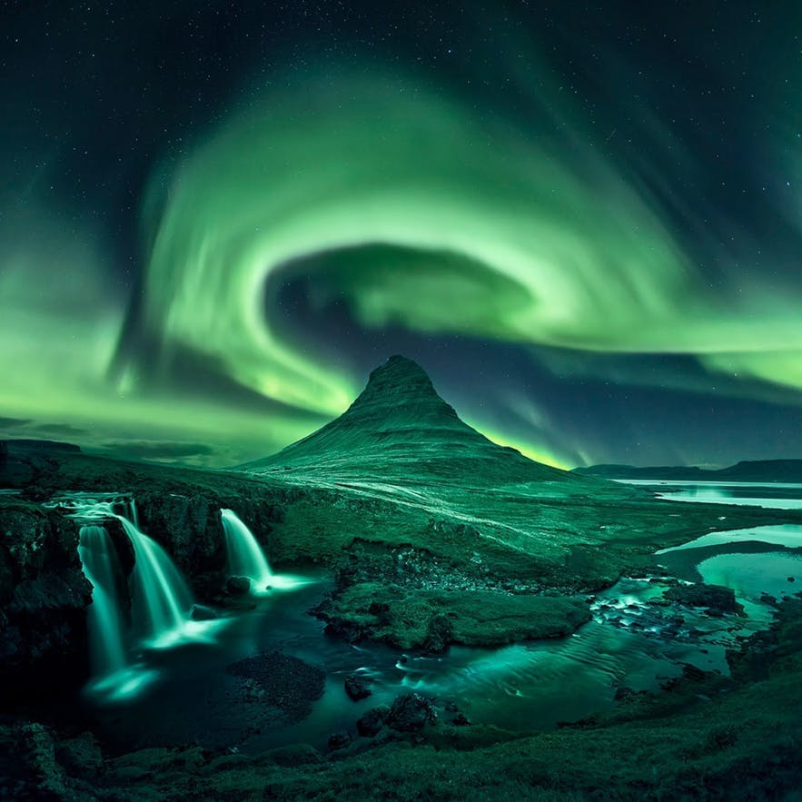 The northern lights illuminate the landscape and mountain in green - Iceland Photography | Everything You Need To Know