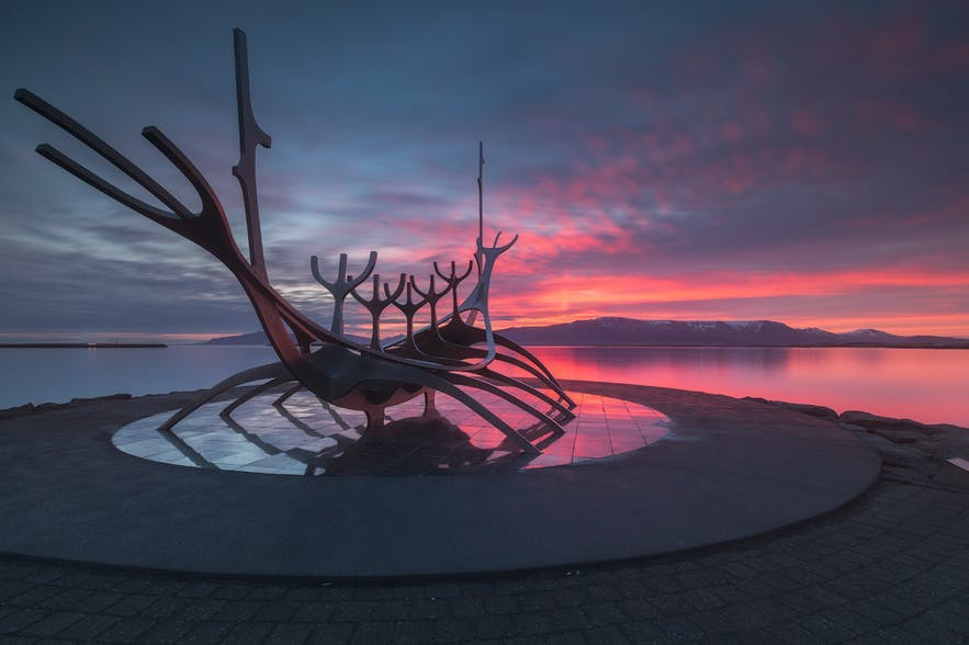 A statue of a wooden boat sits on the water's edge as the sun sets behind - Iceland Photography | Everything You Need To Know