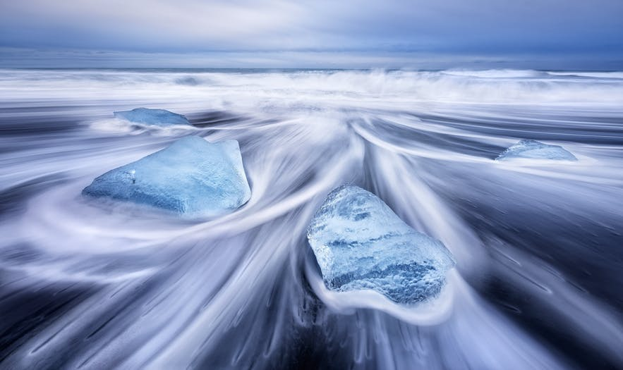 Water rushes around two blocks of ice on the coast - Iceland Photography | Everything You Need To Know