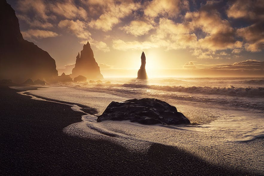 A black sand beach landscape photograph showing columns of rock in the sea - Iceland Photography | Everything You Need To Know