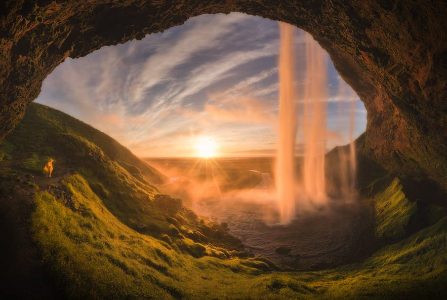 A waterfall and rising sun is beautifully framed by a cave - Iceland Photography   Everything You Need To Know