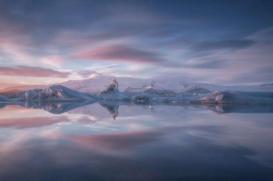A row of glacial mountains are reflected in a glacial lagoon - Iceland Photography | Everything You Need To Know